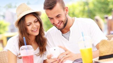 A picture of a happy couple using smartphone in a cafe